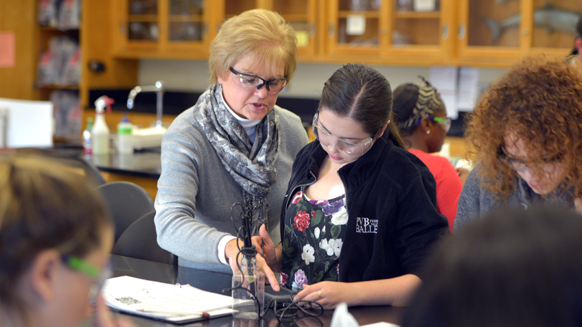 A science teacher assisting a college student at a lab table