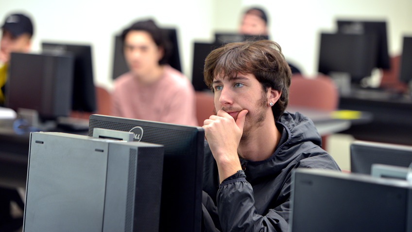 A male college student using a computer in a computer lab