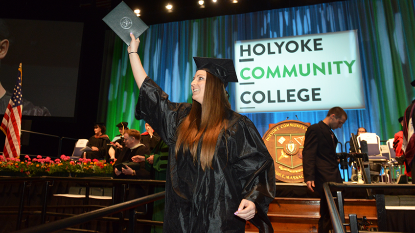 A smiling female HCC graduate wearing her cap and gown, holding her diploma at Commencement