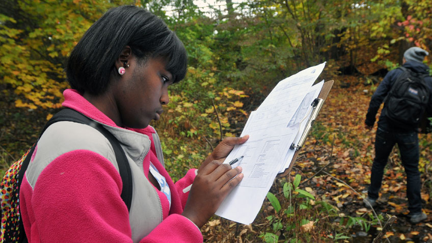 A student takes notes while outside on the HCC campus