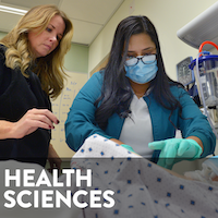 A healthcare student wearing glasses, a mask, and gloves works on a patient simulator. An instructor stands nearby.