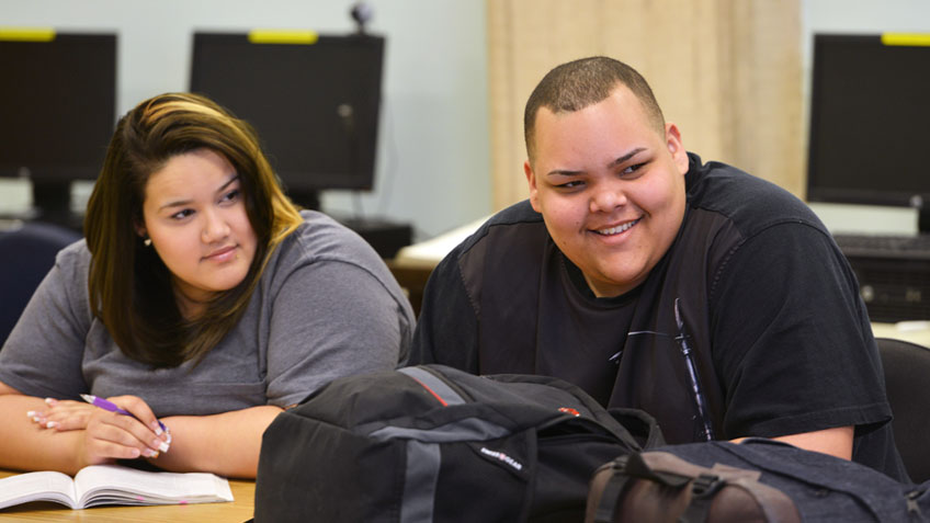 Two students smile in a classroom