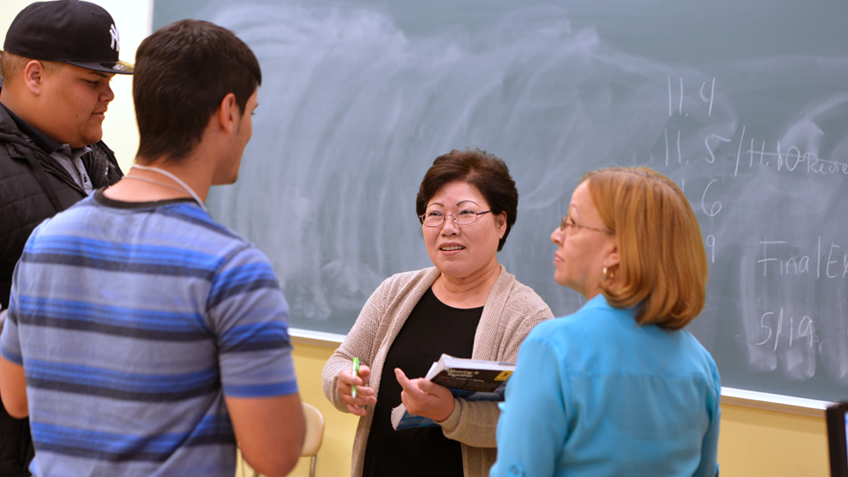 Two HCC faculty members talking with two students in a classroom