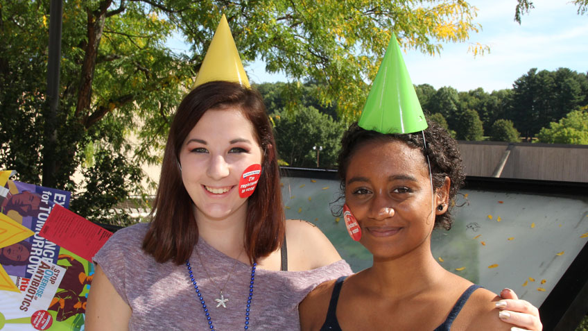 Two smiling students wearing party hats