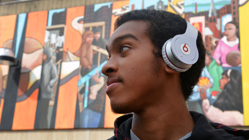 A male african american student wearing headphones stands in front of a mural