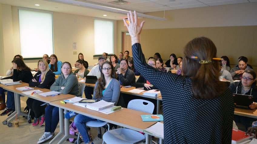 A teacher raising her hand before a classroom full of students