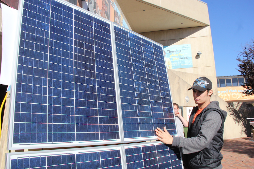 Male student standing beside solar panel