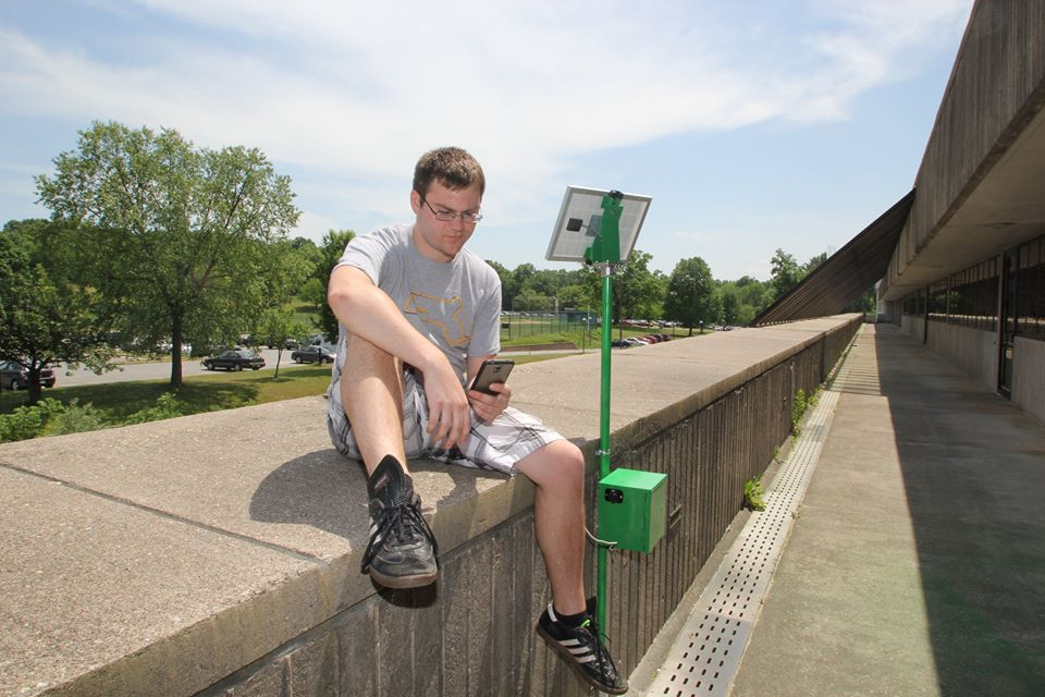 A male student charges his phone at a solar charging station