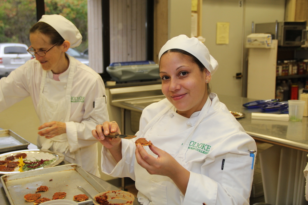 A student prepares food for HCC's Sustainable Harvest Dinner