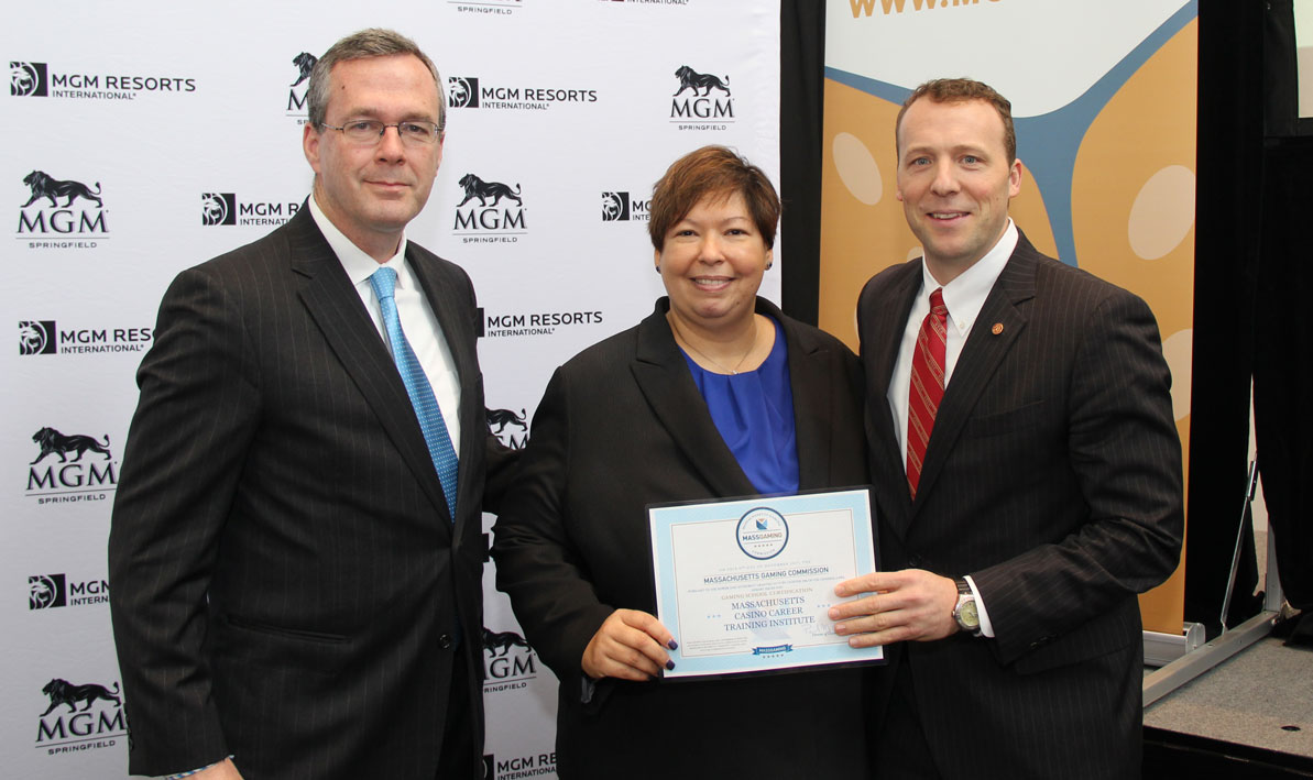 Bruce Stebbins, Massachusetts Gaming commissioner, awards a gaming school certificate to HCC president Christina Royal and STCC president John Cook.