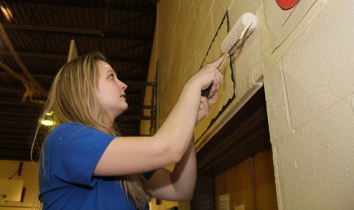 HCC student Amanda Rooke paints the Kelly Elementary School gym.