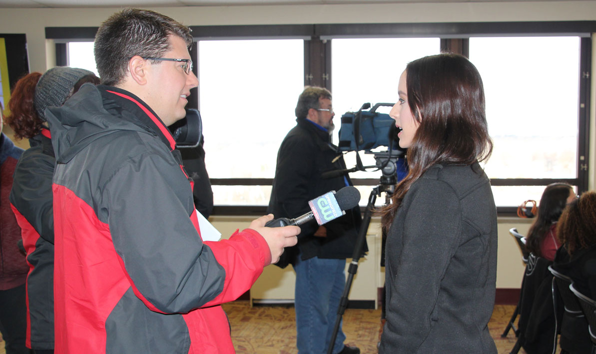 HCC student Alexandra Santiago, a recent evacuee from Puerto Rico, talks to a TV reporter during a press conference.