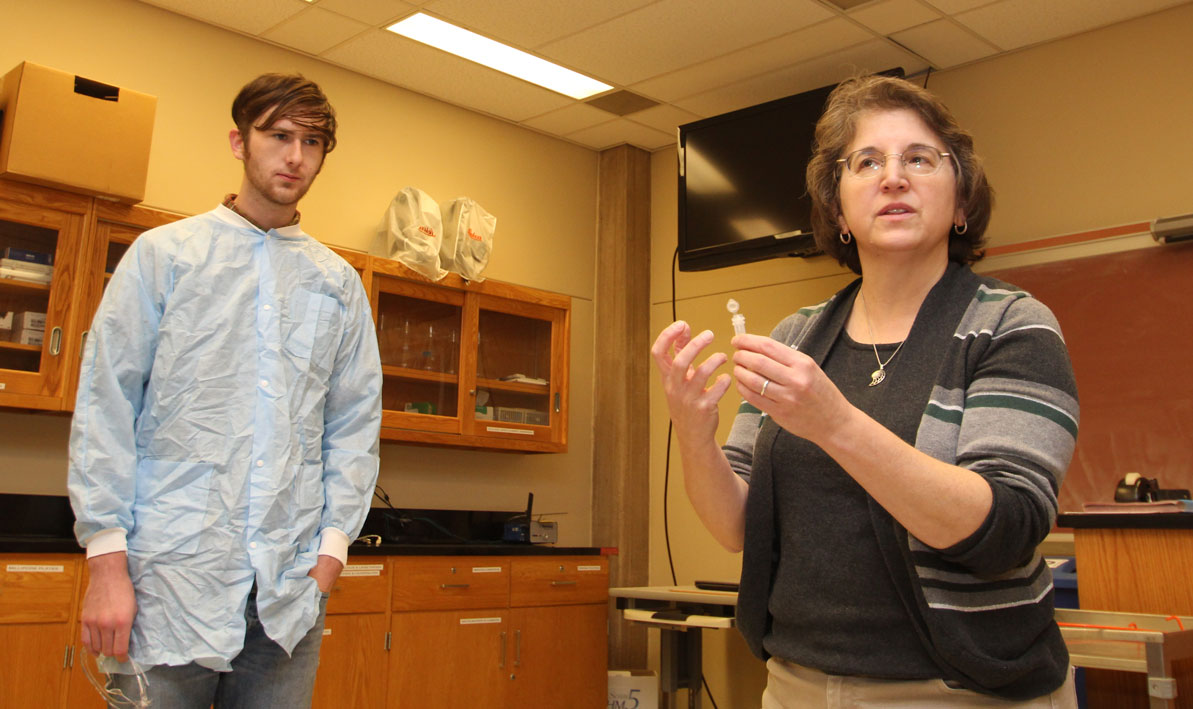 Honors biology professor Carolyn Wetzel talks to students during lab.