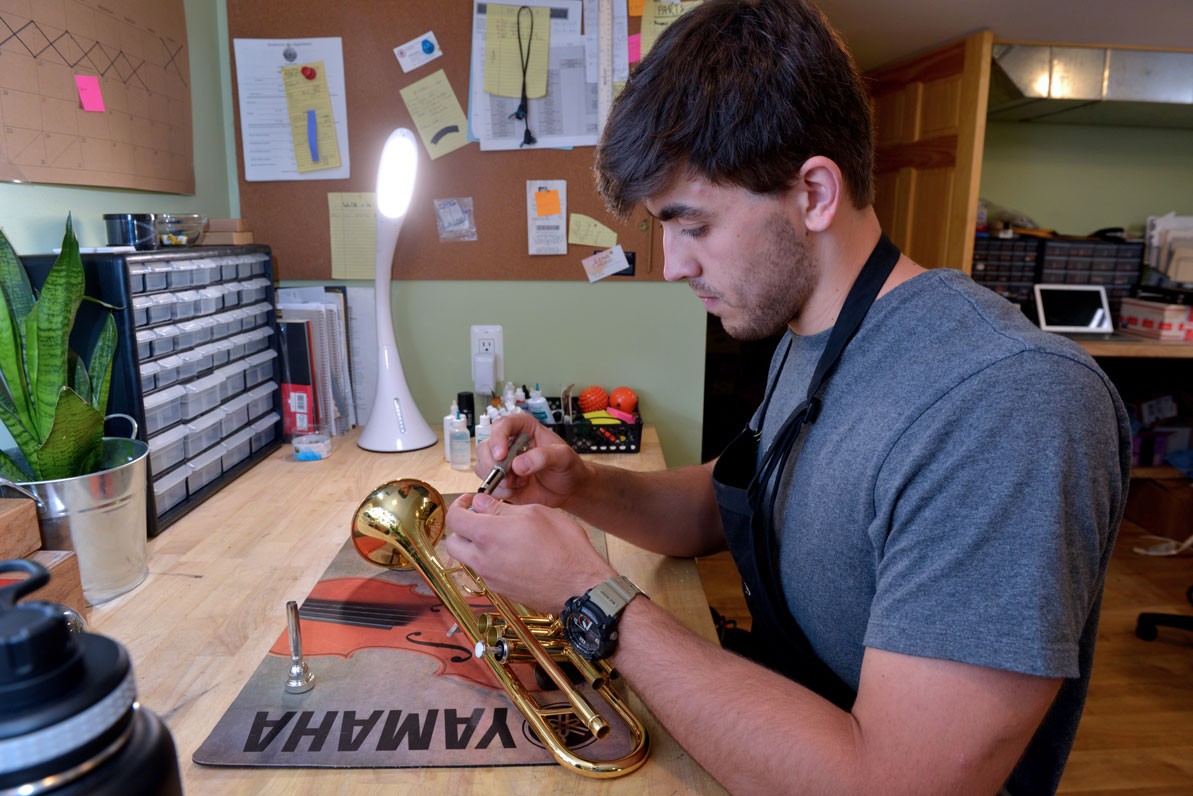 David works on a trumpet in the family's musical repair shop.