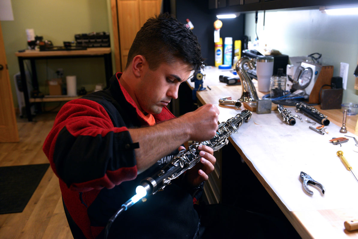 Filipp repairs a clarinet in the Dubchaks' basement workshop.