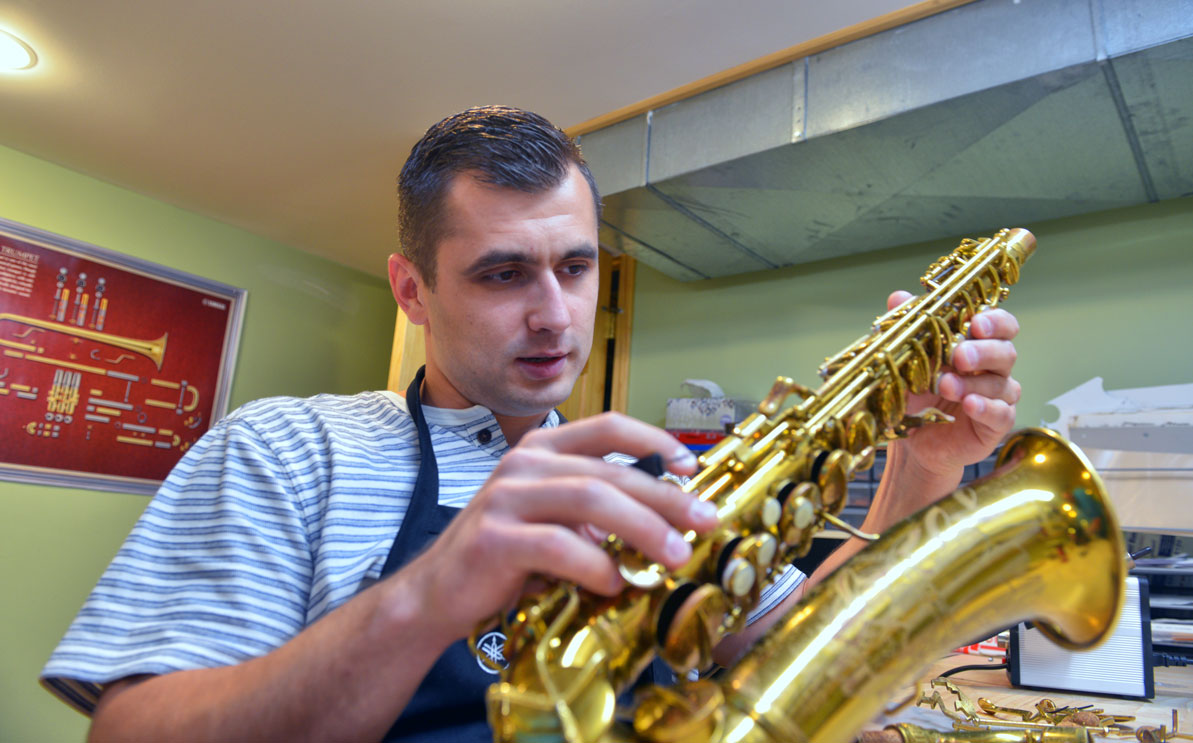 Roman repairs a saxaphone in the Dubchaks' basement workshop.