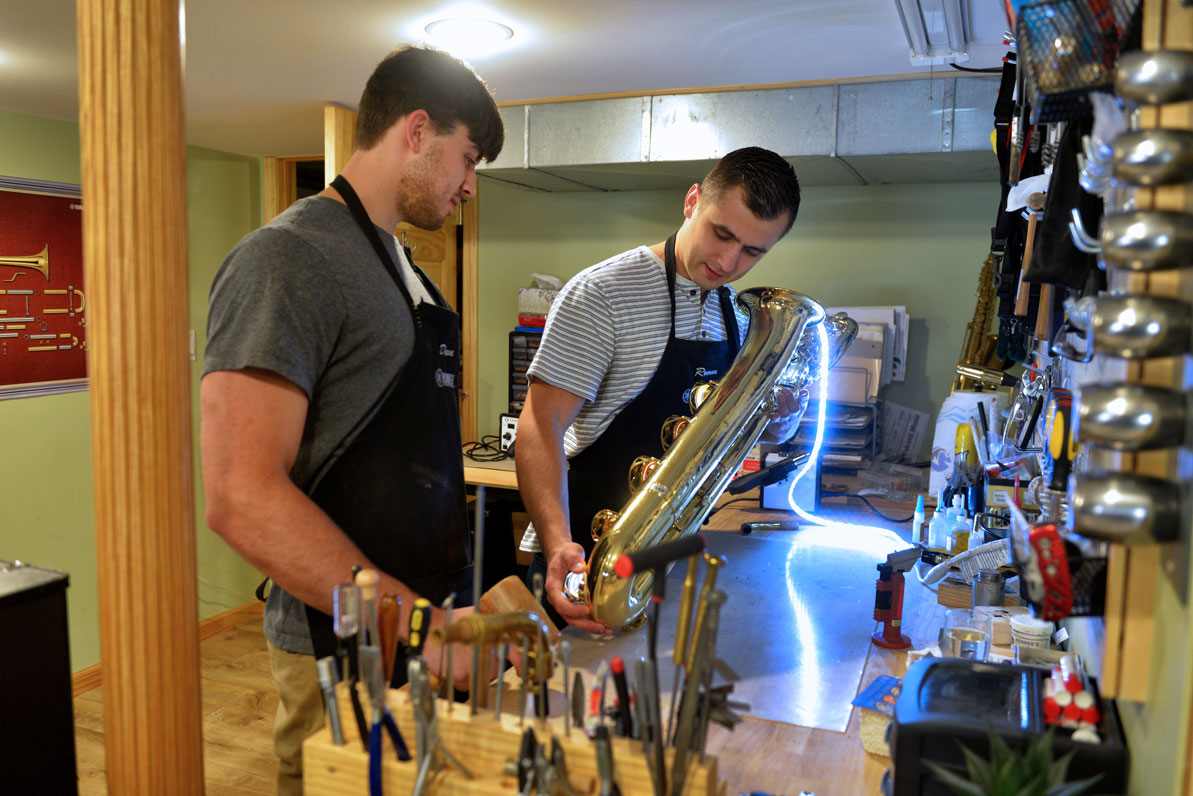 David '17 and Roman '17 work on a baritone saxophone in their basement workshop.