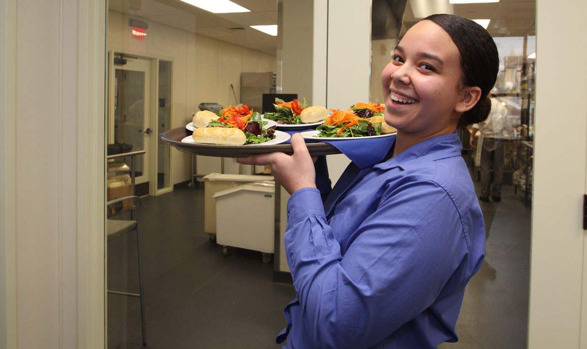 An HCC student gets ready to serve lunch at the HCC MGM Culinary Arts Institute