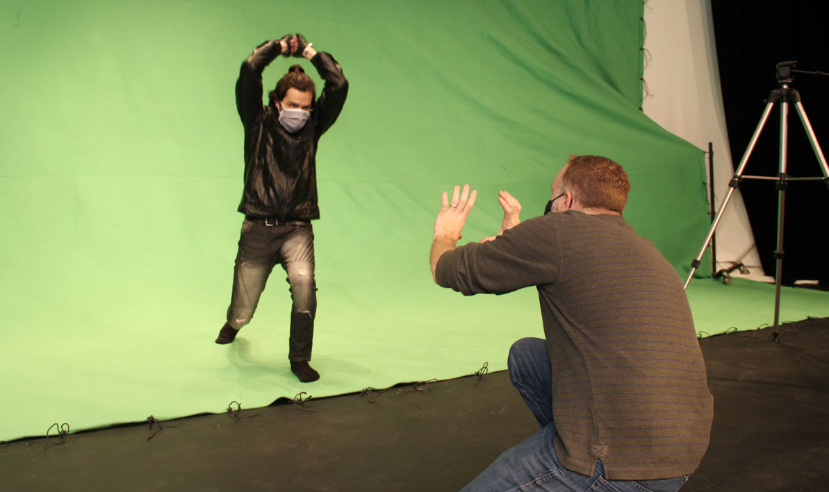 Director Tim Cochran, right, and alumni actor Mike Pray rehearse a scene from Fatal Fisticuffs in front of a green screen on the state of the Leslie Phillips Theater.