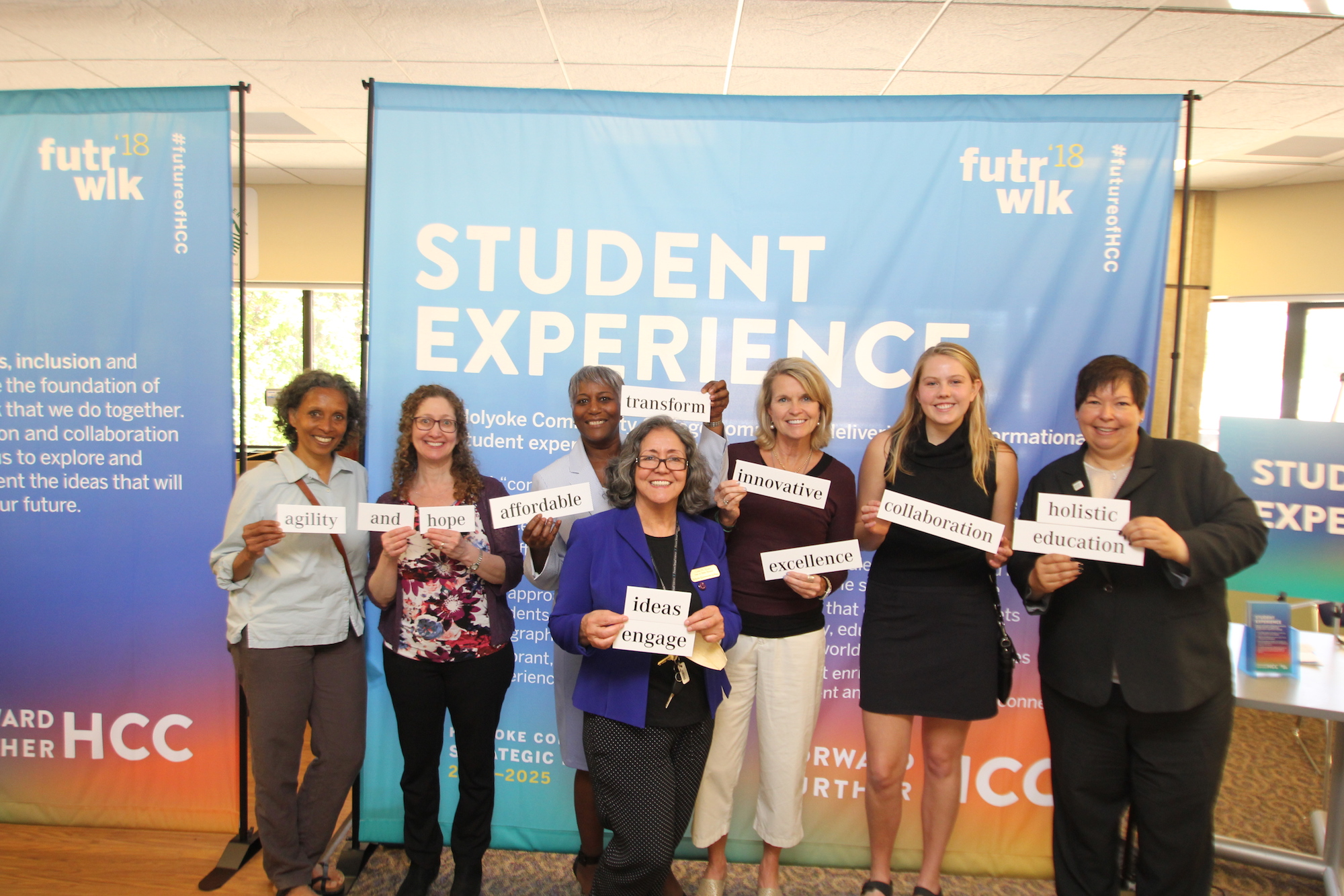 "HCC President Christina Royal poses with community members at the Future Walk event. They are each holding an inspirational word printed on a large piece of paper. Words include ""agility,"" ""hope,"" ""affordable,"" ""innovative,"" and ""collaboration."""