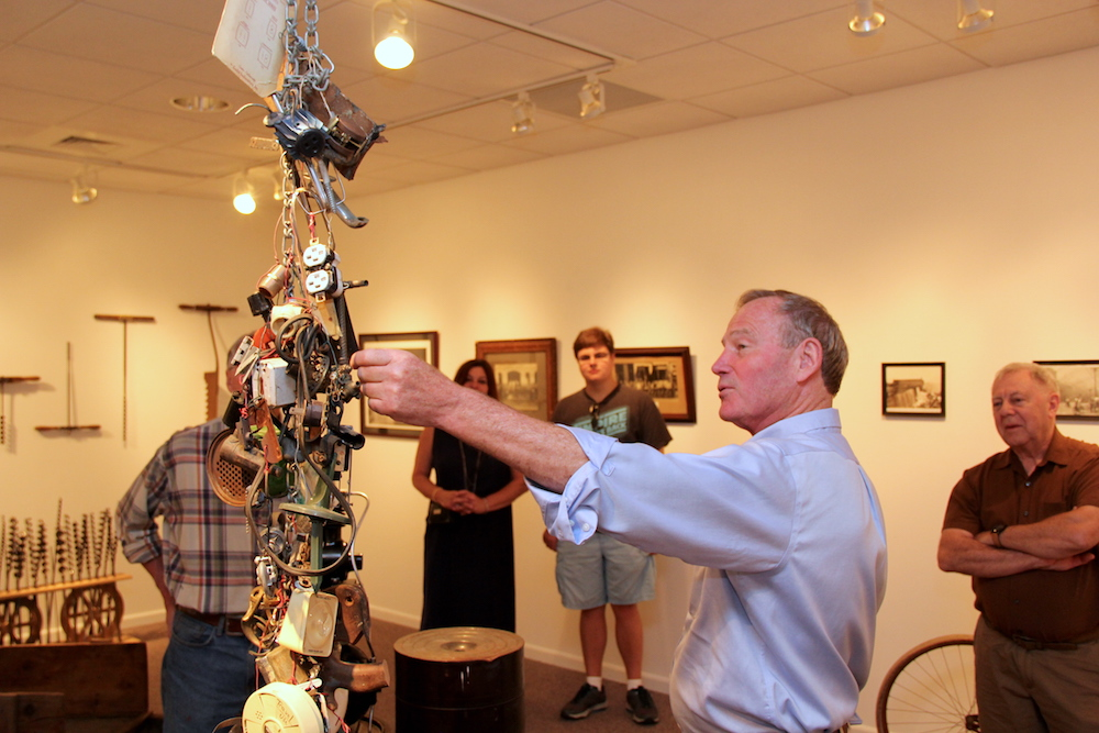 A man touches an art installation made of hardware in Taber Art Gallery