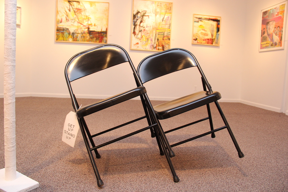 Two metal folding chairs leaning against one another