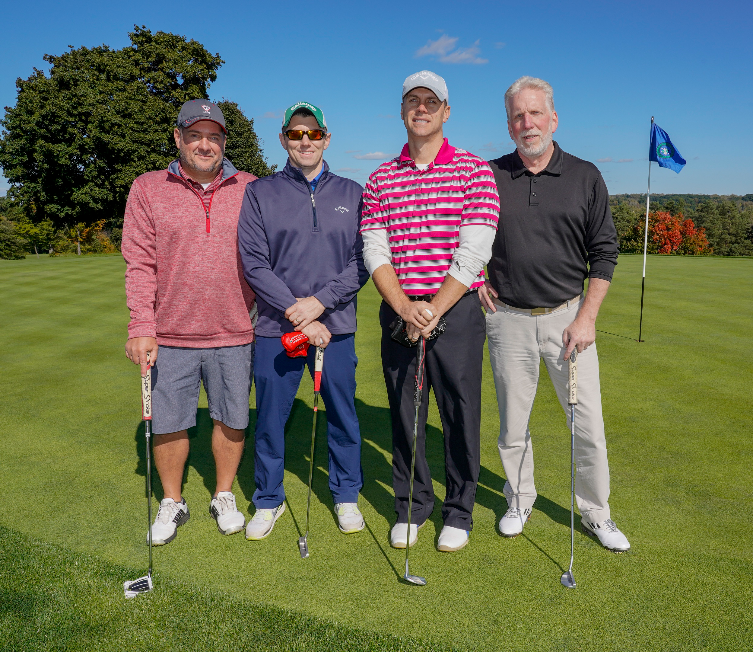 Four men wearing hats stand on a golf course. One holds a golf club.