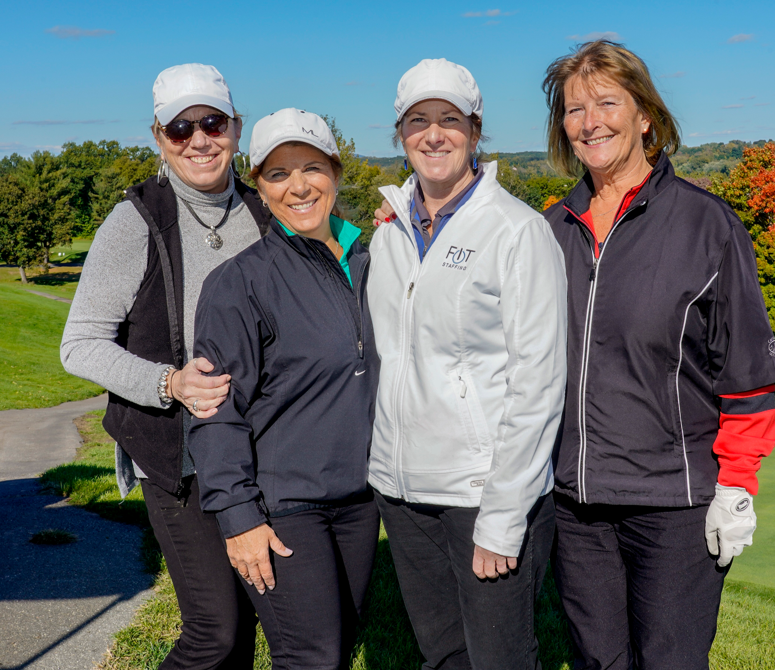Four women stand, smiling, on a golf green.