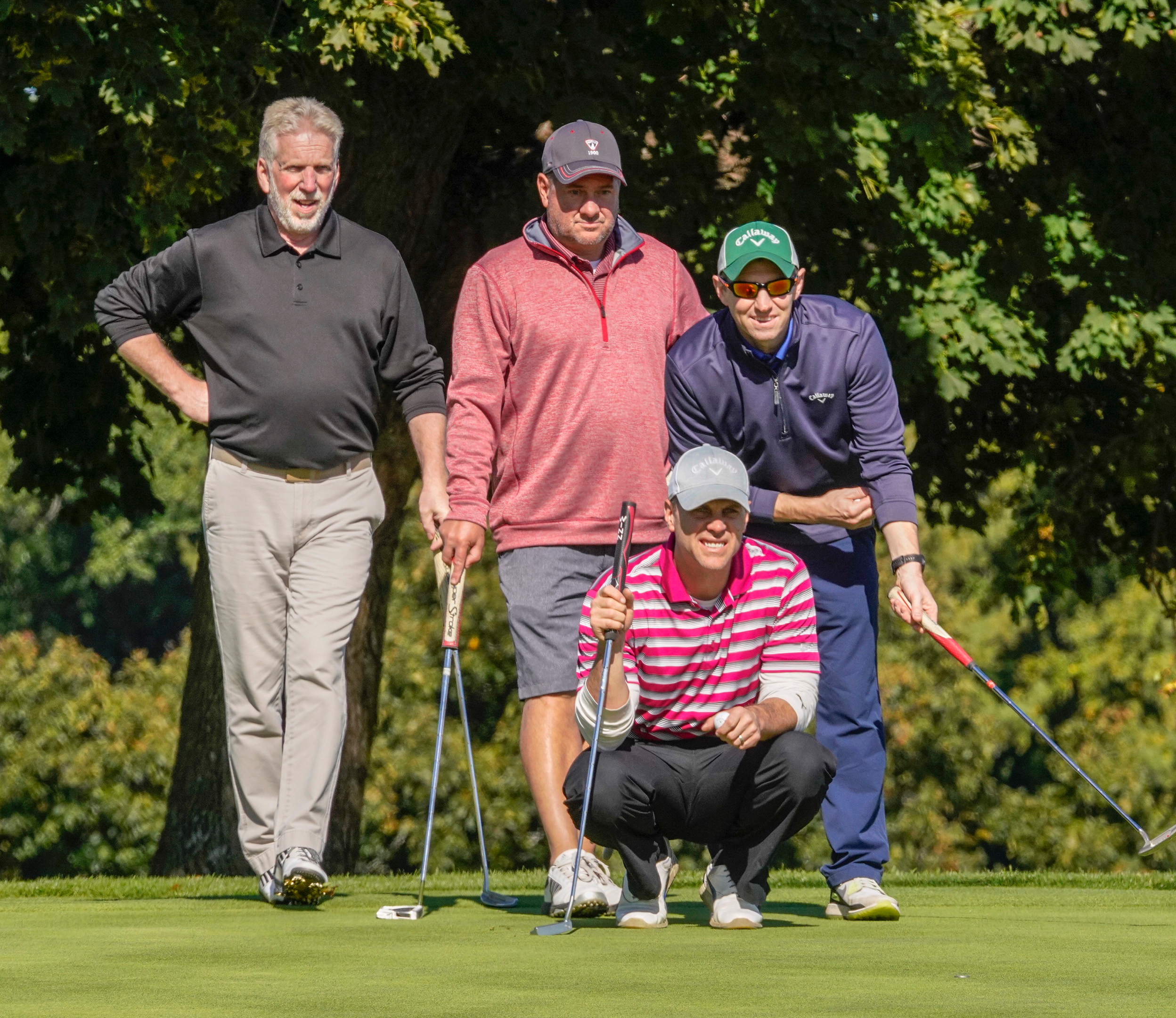 Four people stand on a golf green. One crouches, looking toward a cup.