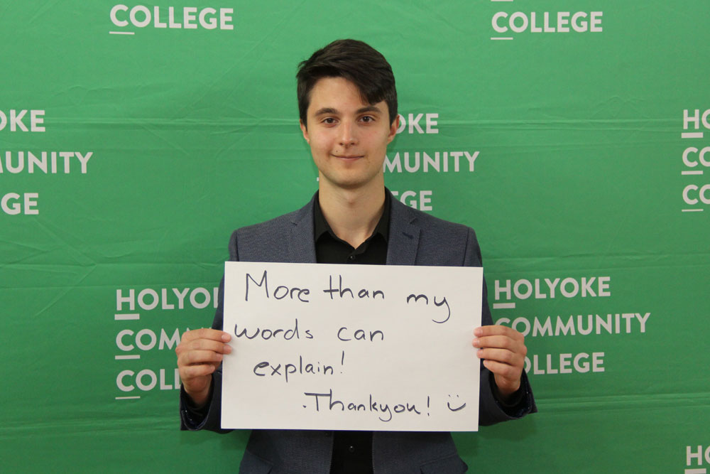 "A male student holds a handwritten sign that reads ""More than my words can explain! Thank you!"""