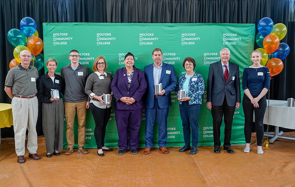 Group photo of individuals at the 2019 scholarship reception posing in front of a green HCC backdrop