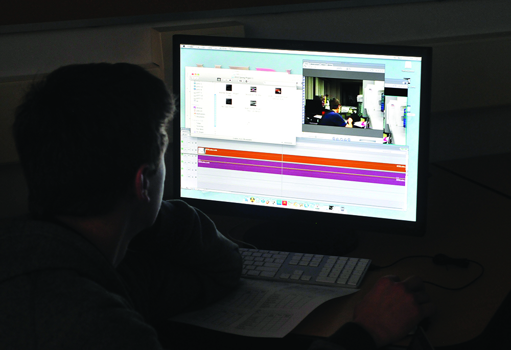 An electronic media student works on a computer