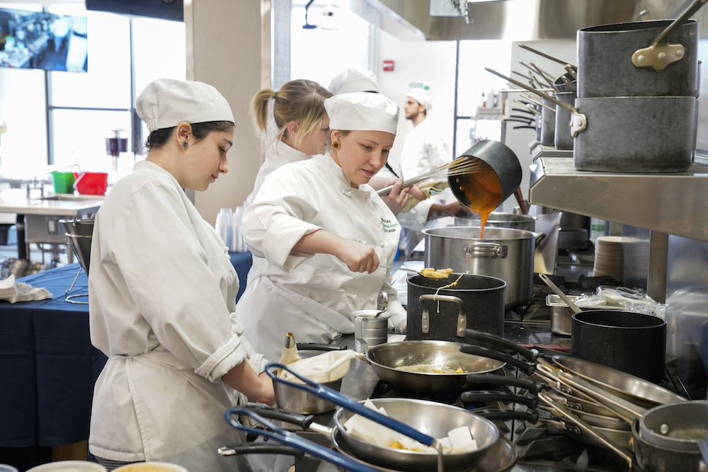 Two students cooking in a culinary arts kitchen