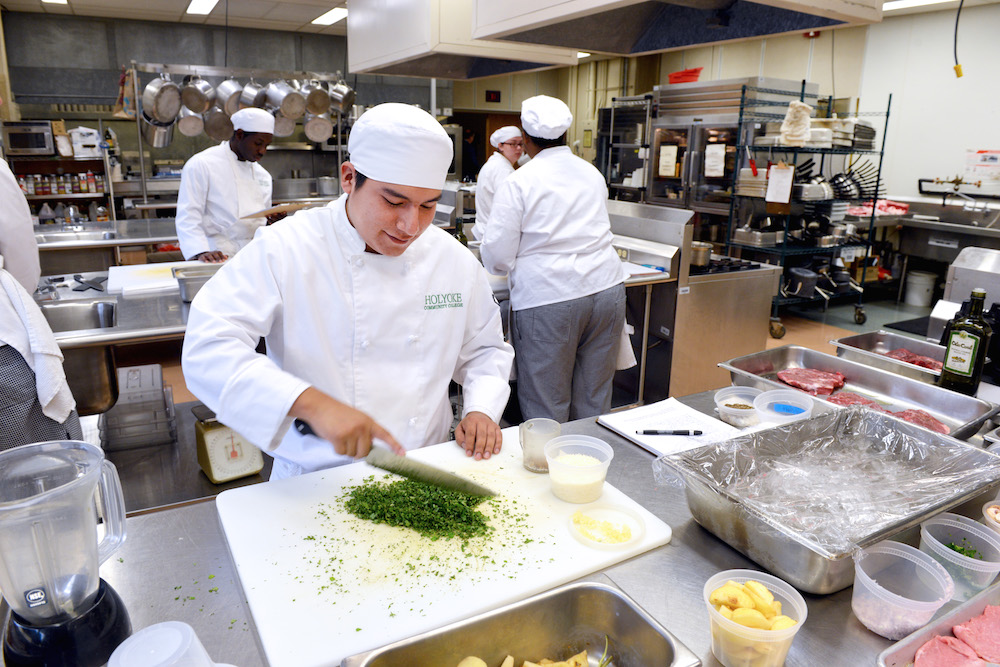 A culinary arts student chops herbs in the classroom kitchen