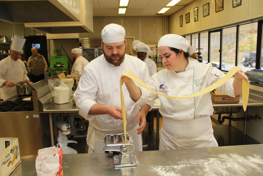 Two culinary arts students use a pasta maker