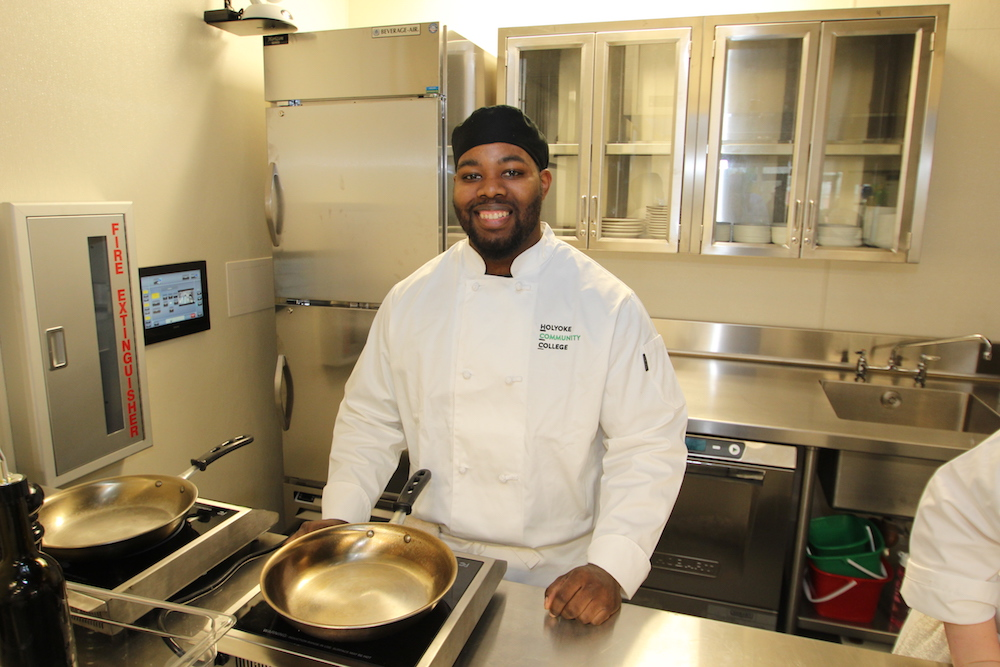 A culinary arts student smiles