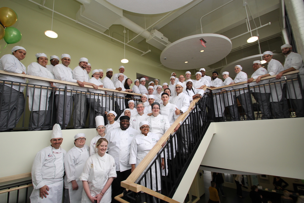 A group of culinary arts students posing on the stairs in the HCC MGM Culinary Arts Institute