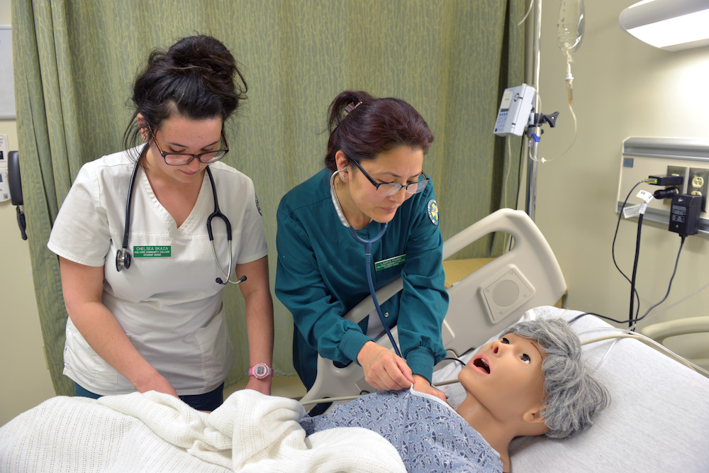 Two health students work with a patient simulator
