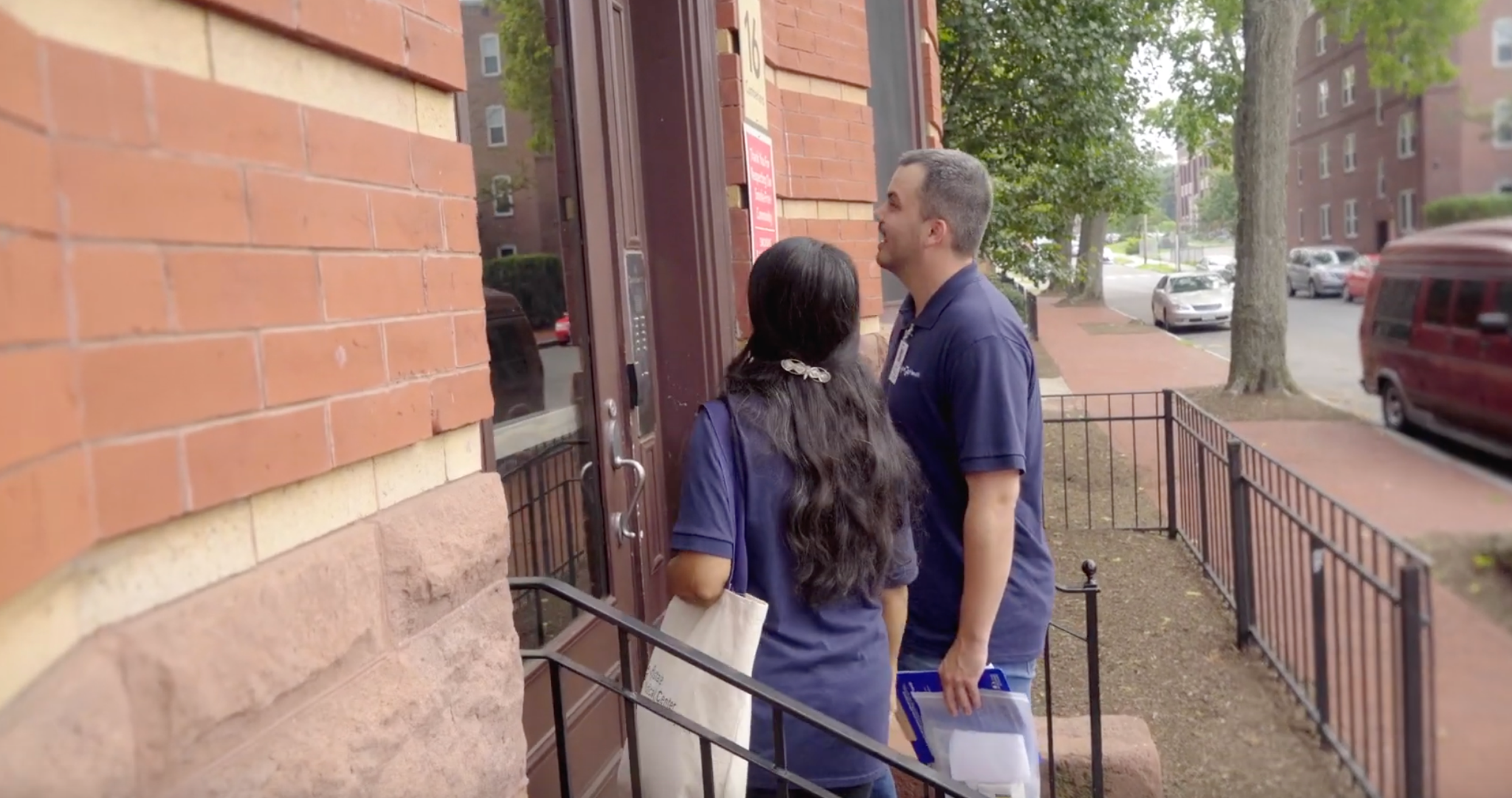 Two community health workers approach the front door of an apartment building