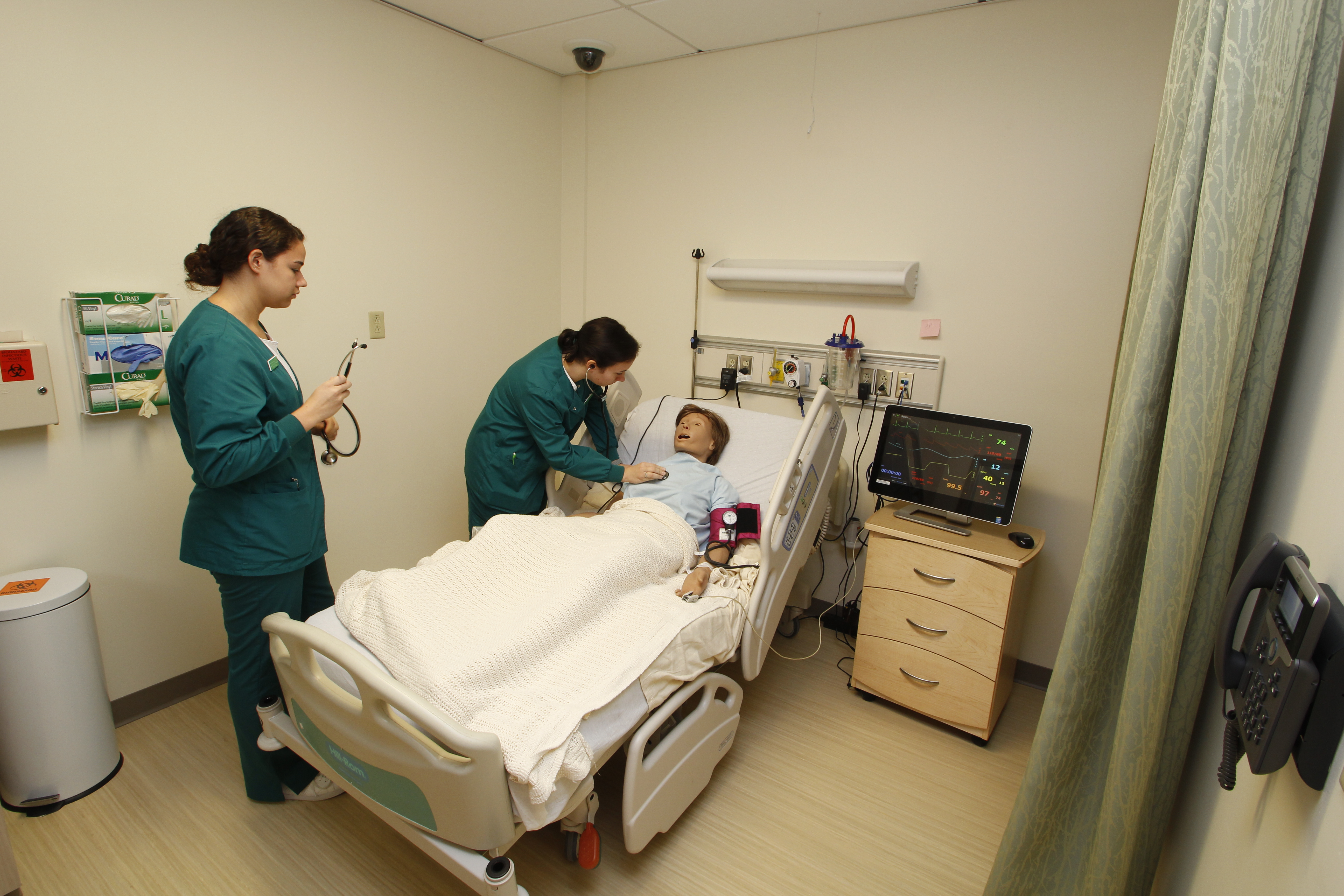 Two medical assistant students practice on a patient simulation