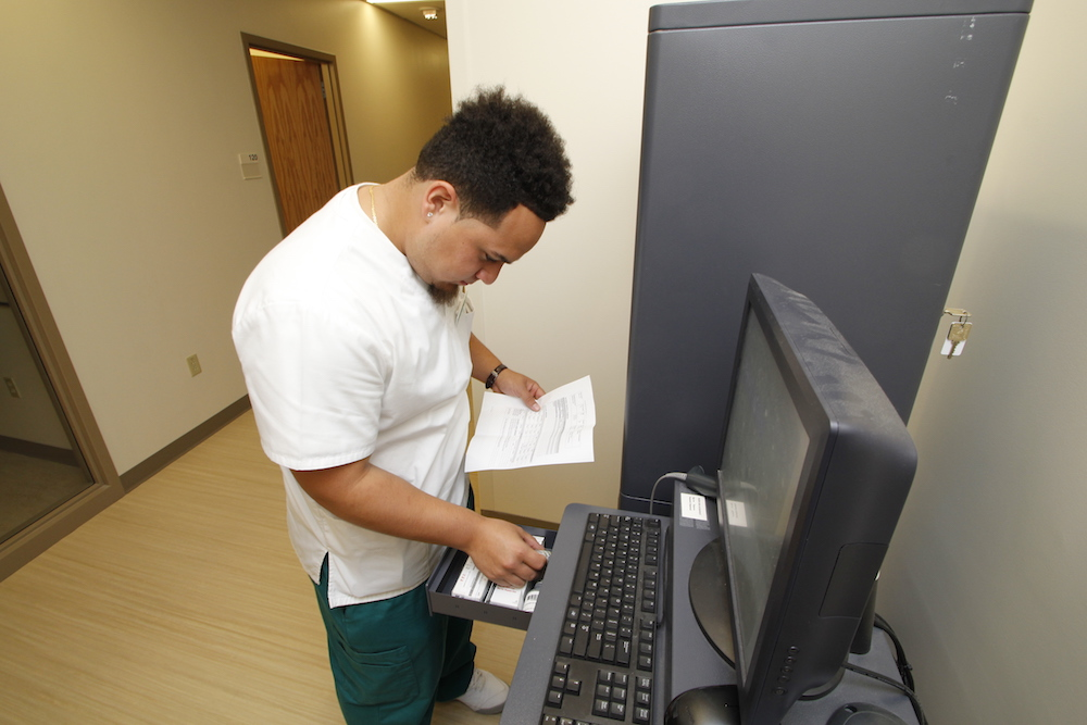 A male medical assistant student opens a drawer