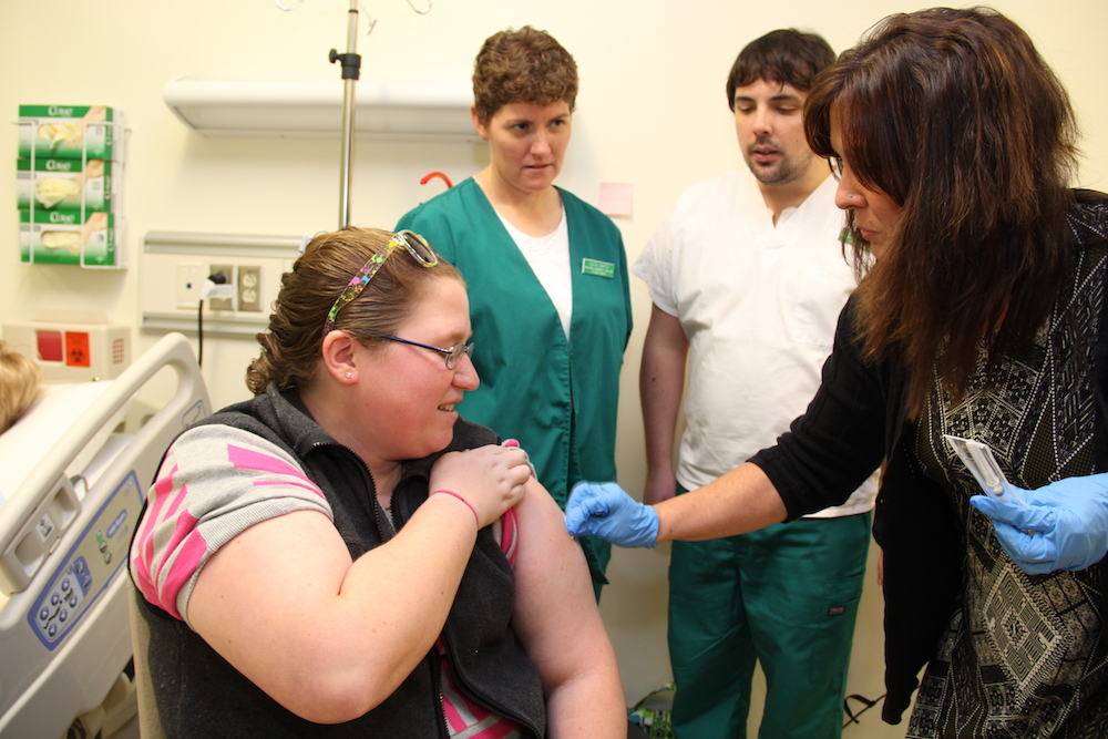 Medical assistant students observe as a flu shot is administered