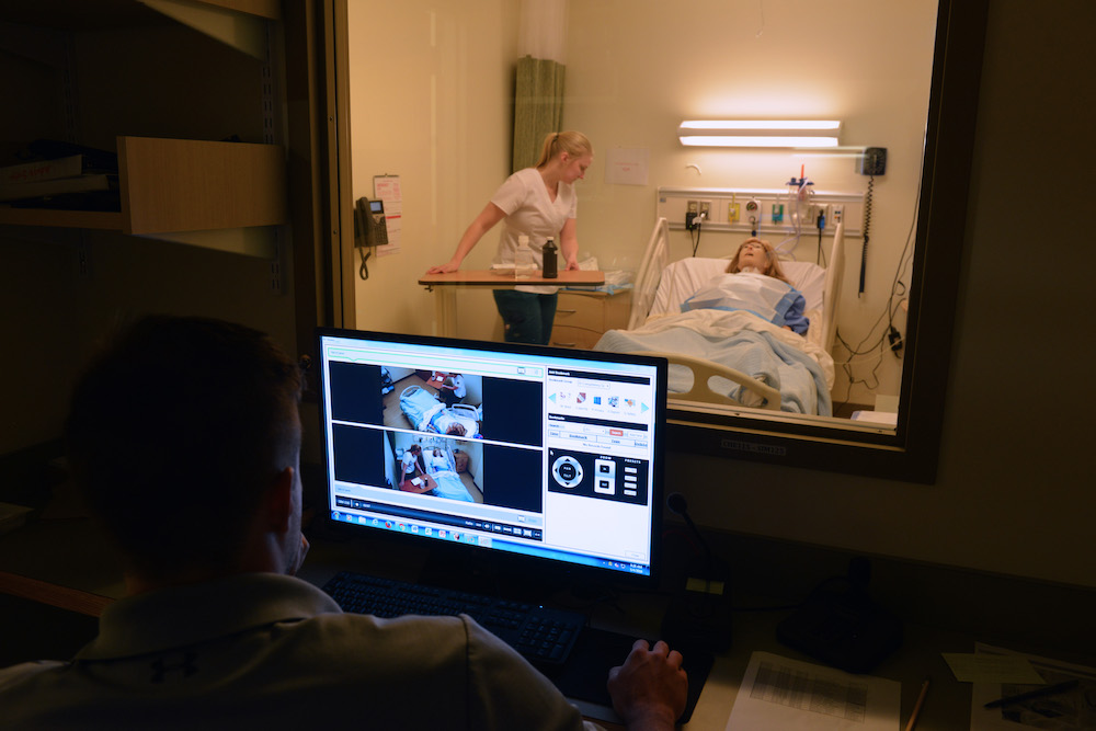 A computer monitors a female nursing student working with an adult patient simulation