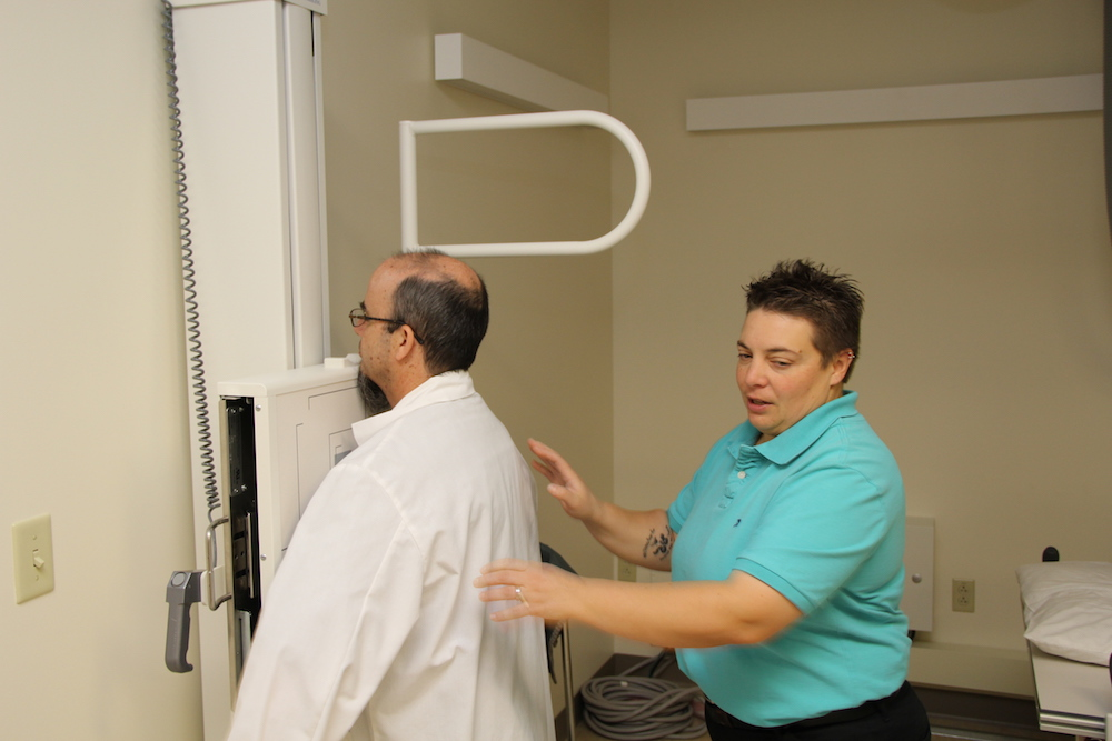 An instructor and a radiologic technology student demonstrate correct positioning
