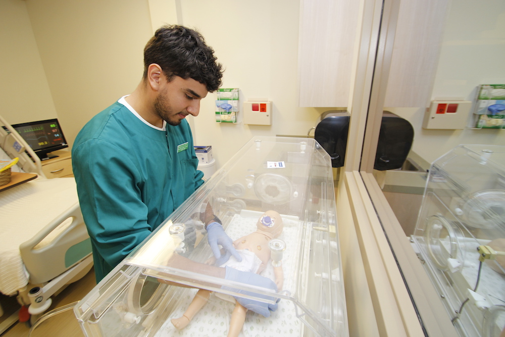A healthcare student adjusts the oxygen mask on an infant simulator