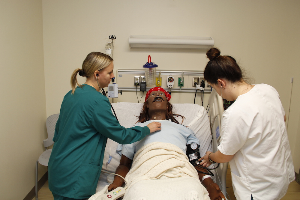 Two healthcare students practice on a patient simulator