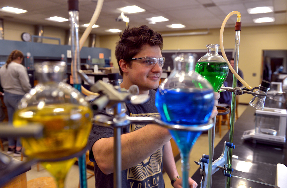 A chemistry student smiles while examining glass containers of colored liquid