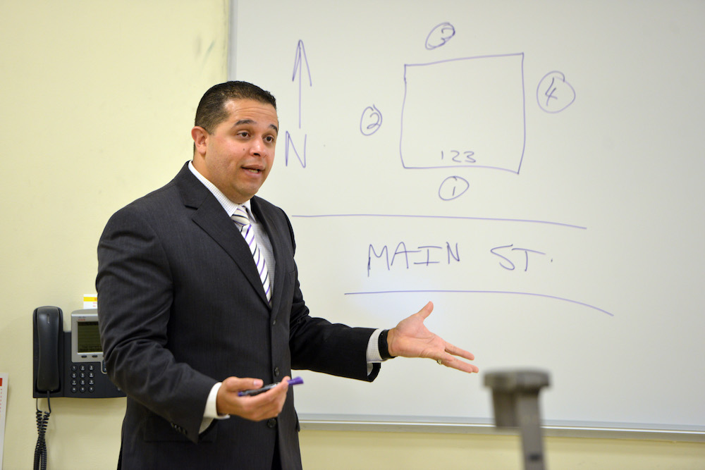 A criminal justice professor teaches in front of a map drawn on a whiteboard