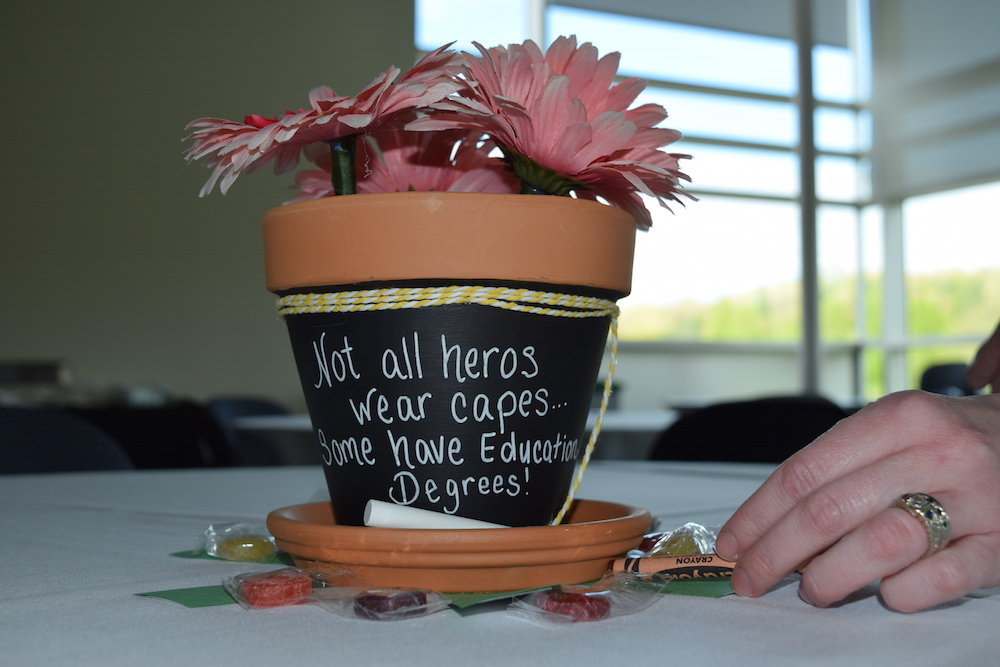 "A plant pot that reads ""Not all heros wear capes. Some have education degrees."""