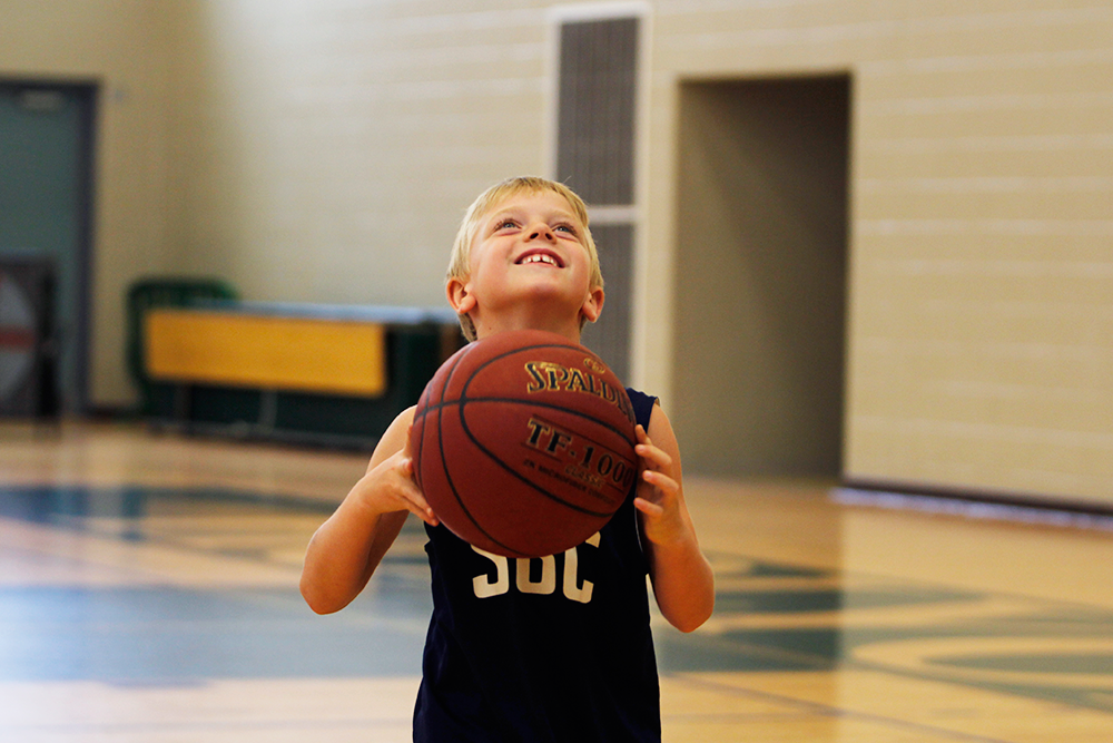 A young child prepares to shoot a basketball